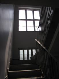 The two empty windows in the stairwell before the new glass design