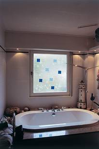Instead of common ornamental glass, this bathroom window features an installed melted-glass pane (Fusing pane) with shaped mussels and sea stars.